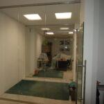 Szklane ściany działowe znaświetleniem idrzwiami uchylnymi prawymi otwartymi