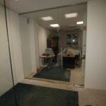 Szklane ściany działowe znaświetleniem idrzwiami uchylnymi prawymi zamkniętymi